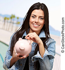 portrait of young woman saving with piggy bank near the...
