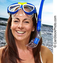 portrait of a happy middle aged woman wearing snorkel and...