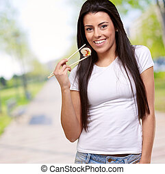 portrait of young woman eating sushi at park