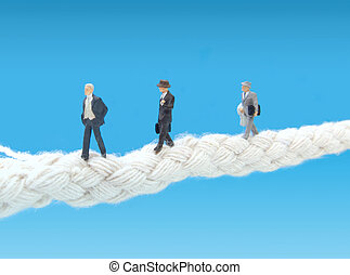 Businessman walking tightrope - Miniature businessman...