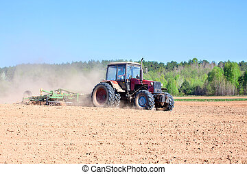 Ploughing tractor during cultivation agriculture works at...