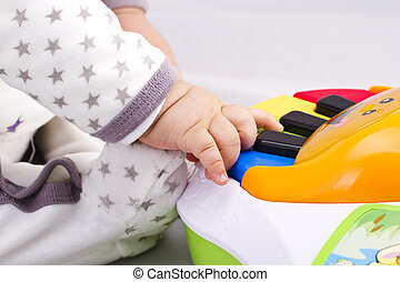 Newborn baby boy playing with a toy piano