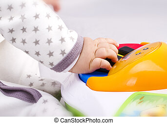 Newborn baby playing with a toy piano