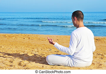 meditation - yogi man dressed in white meditating on the...