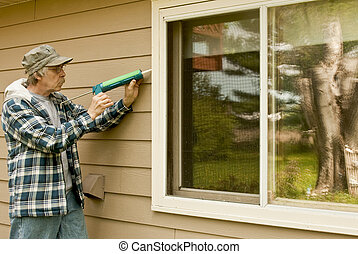 man using a caulking gun - workman sealing an exterior...
