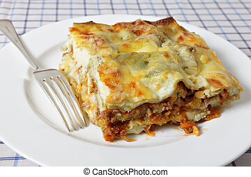 Lasagne slice with fork - A slice of lasagne verde on a...