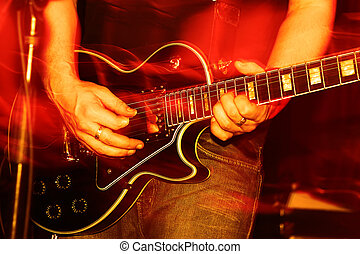 Live Concert - closeup of an guitarist at a rock concert,...
