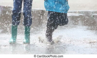 More splashes - Boy and girl having fun on a rainy day...