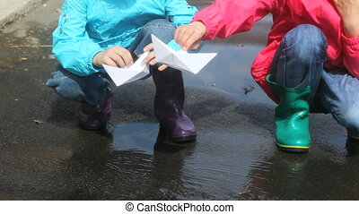 Springtime entertainment - Children playing with paper boats...
