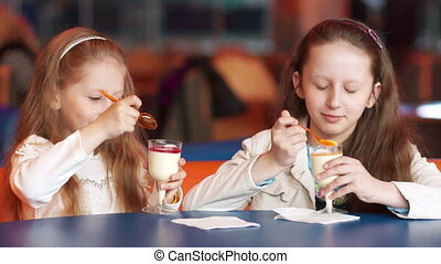 Two sisters eat ice cream at a cafe