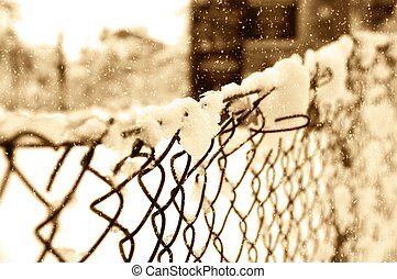 Snow on a wire mesh fence - Sepia toned image of falling...