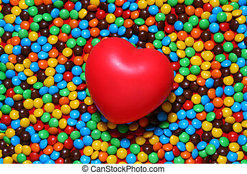 Soft red heart over candy background - Colorful candy...