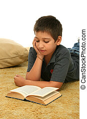 Boy reading a book on the floor - Boy in a room reading a...
