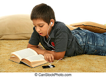 Boy reading and listening music - Boy studing laying down...