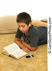 Boy reading and listening music - Boy studying laying down...