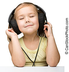Cute little girl enjoying music using headphones, isolated...