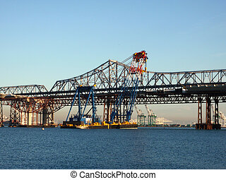 Large Crane on Barge lifts section of bridge into place -...