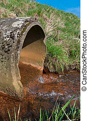 drain pipe - water flowing from a drain pipe into a small...