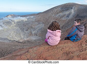 Girl and boy sitting on the rim of volcano crater of Vulcano...