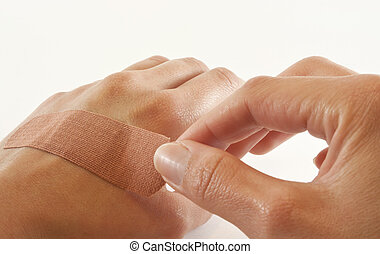 Two hands with bandage - One bare female hand sticking...