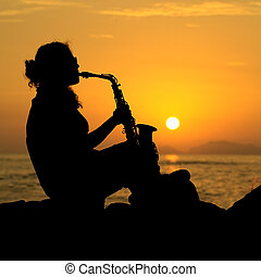 Woman Playing the Saxophone - The silhouette of a young...
