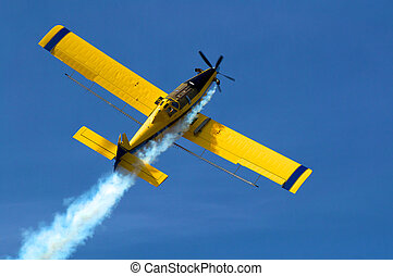 Crop duster at work applying chemicals to field