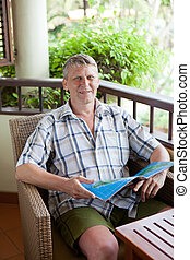 mature man sits on a balcony of tropical hotel with the...