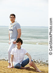 Near shallow water - Young gay couple spending a sunny day...