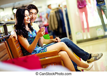 Modern tech in shopping mall - Young people using a smart...