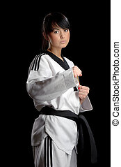 Taekwondo. Woman in a kimono on the black background -...