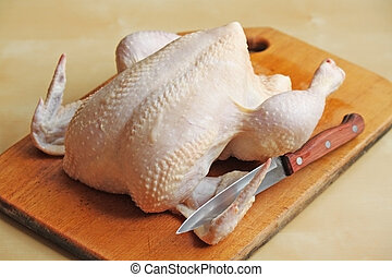 Whole raw chicken on the chopping board with a knife