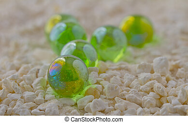 Marbles - Glass green marbles over white sand and little...