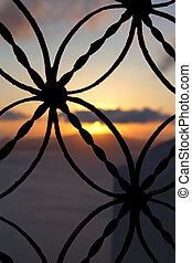 Traditional window at sunset - Traditional metallic fence on...