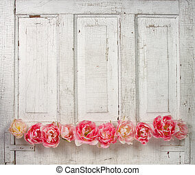 Flowers on a paneled vintage door, (pink tulips or roses...