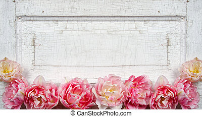 Flowers on a paneled vintage door, pink tulips or rose like...
