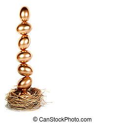 Golden eggs balanced in a nest (nest egg) - Golden eggs...