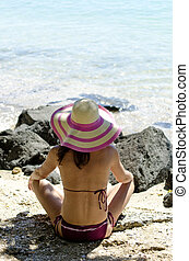 Woman sitting on beach wearing hat - A color landscape photo...