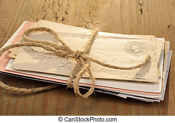Bundle of letters tied with a cord on the old wooden table
