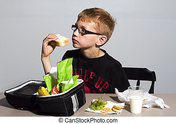 Boy Eating Sandwich - young boy eating his lunch at school -...