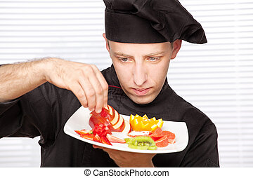 chef decorating delicious fruit plate