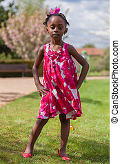 Outdoor portrait of a cute african american little girl,...
