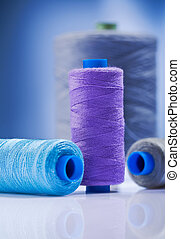 sewing spools on blue background