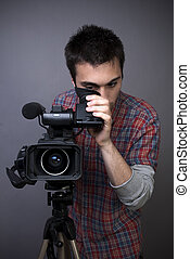 Young man with professional video camcorder on gray...