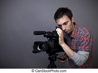 Young man with video camcorder - Studio shot of young man...