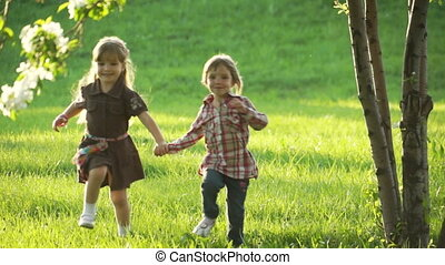 Two girls running at the camera. - Children in the park