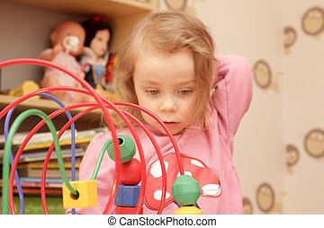 Playtime - Young blond girl playing with a toy
