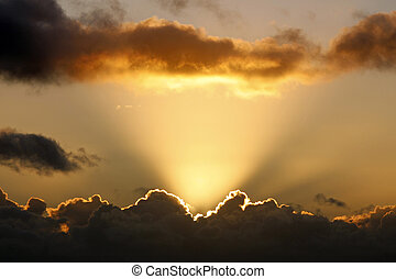 Sun rays and dark clouds at sunset