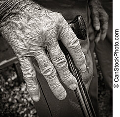 Hand of old man with arthritis supported with walking stick...