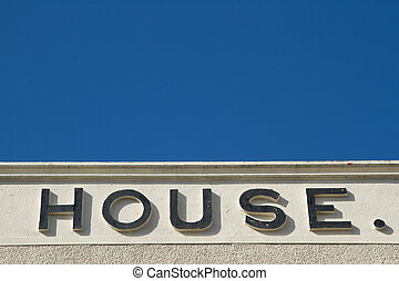 House sign. - A wall with pebble dash and render with the...