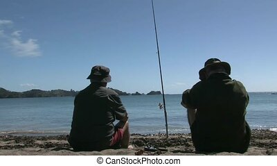 Fishing from the beach - Bay of Islands, New Zealand. two...